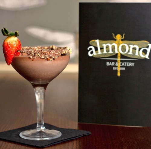 Image of delicious looking cocktail from Almond Bar on table with menu next to it and napkin below it.