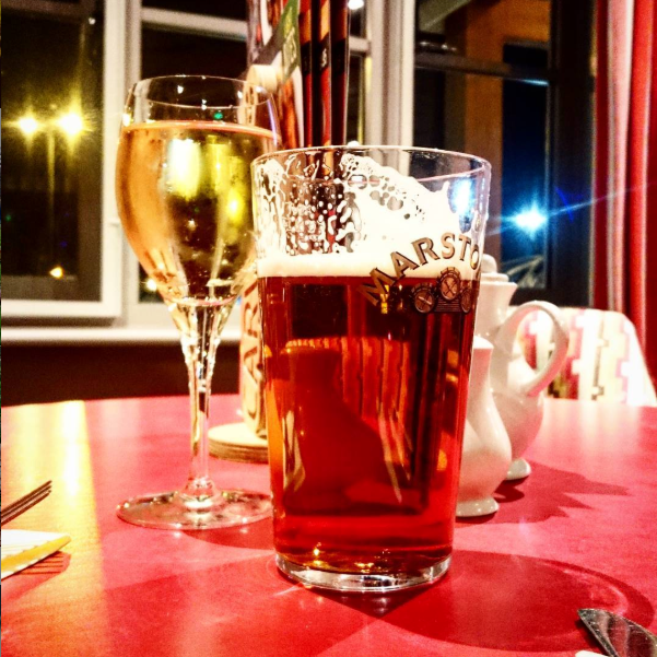 Image taken inside Liverpool pub the Vikings Landing of brightly lit table with half drunk pint and a glass of white wine on table