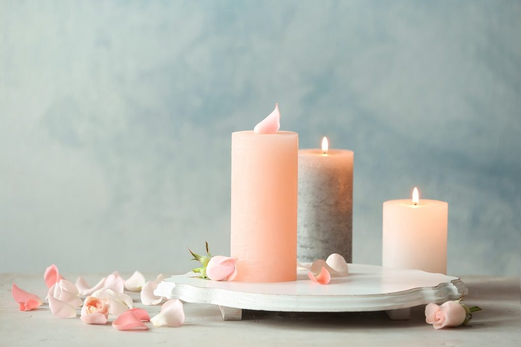 Picture of three pink candles on tray with flower petals