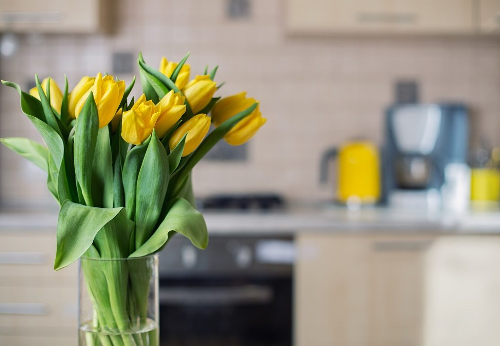 Picture of yellow flowers in the foreground and kitchen in the background