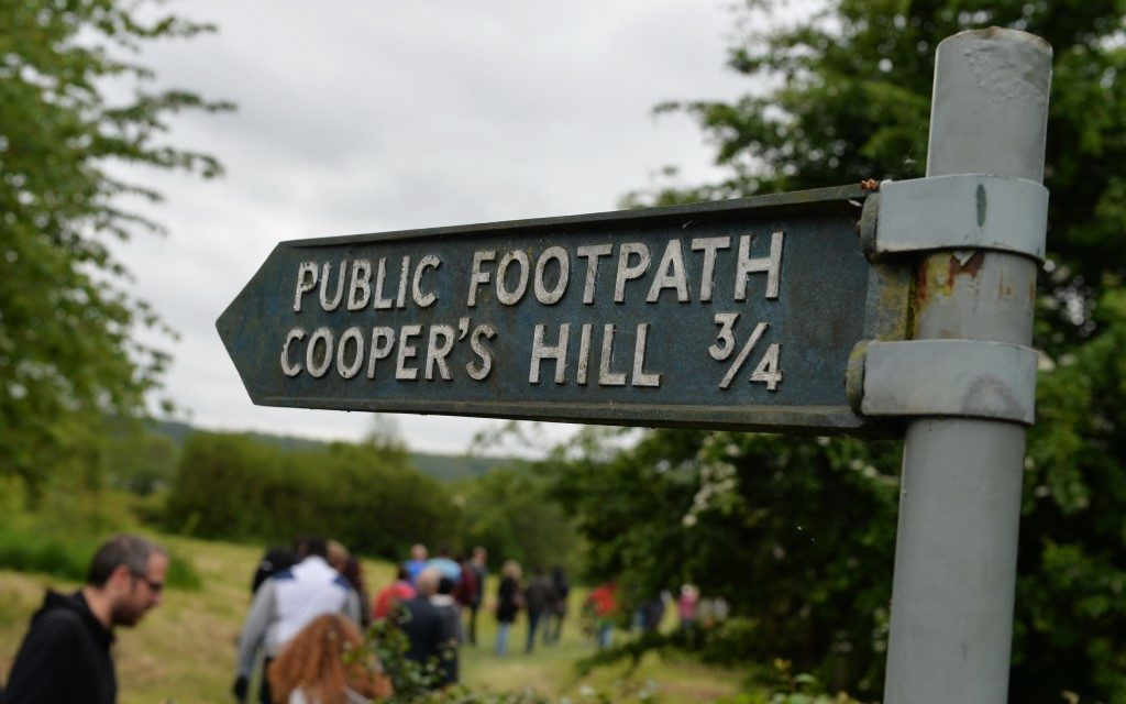 sign pointing to Cooper's Hill with people attending cheese rolling event