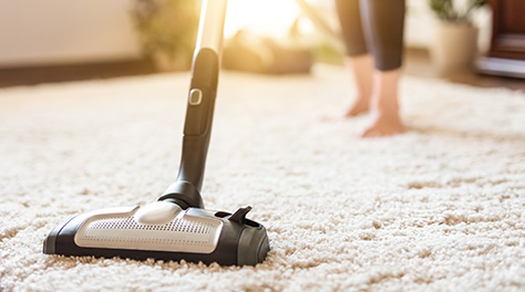 Woman hoovering thick carpet with sun shining through the window